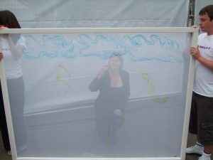 Two people hold a large semi transparent screen. The outline of a woman can be seen on the other side, where she is crouching and drawing.