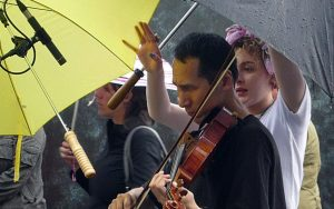 An East Asian man playing viola with audience around him and umbrella over him