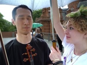 An East Asian man holding his viola under an umbrella held up by his access worker.