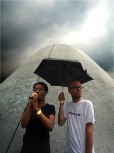 A low angle shot of a black woman speaking into a microphone next to a white man holding an umbrella over their heads, with a giant cone in the background.