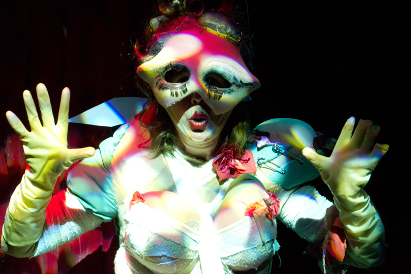 A closeup of a burlesque performer with her yellow gloved hands up, fingers spread. She is wearing a distorted red and white patterned eye mask and crisscrossing bandages across her torso.