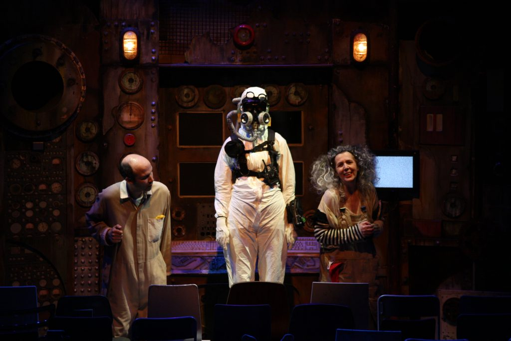 A trio of performers on stage. From left to right, a bald white man wearing a beige jumpsuit with his neck craned to the middle, a person wearing a full body white hazmat suit standing elevated, and an older woman with curly grey hair smiling with hands clutched.