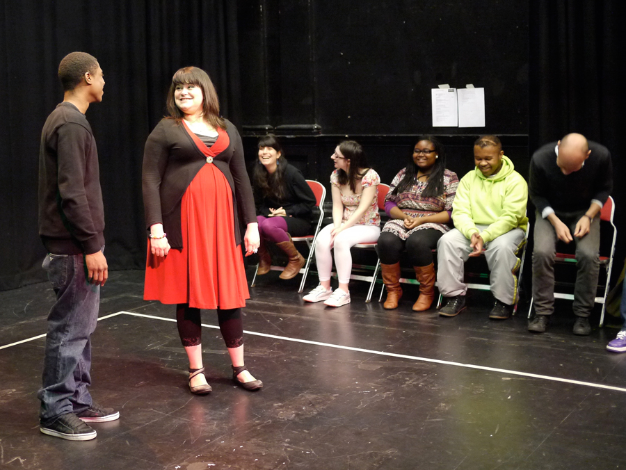 A black male Forum Assistant and a young white female actor perform side by side, smiling in conversation. Five other actors, black and white, look on as audience laughing at them.