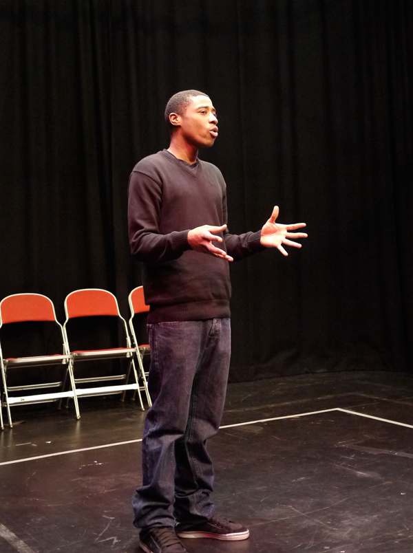 A black Forum Assistant stands centrally, fingers splayed expressively as he explains something to the group, who aren't visible in the shot.