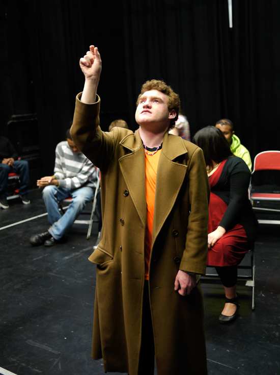 A young white actor playing the role of 'Teacher' stands in a long gold coloured overcoat, looking up and reaching for an imaginary object with his right hand.