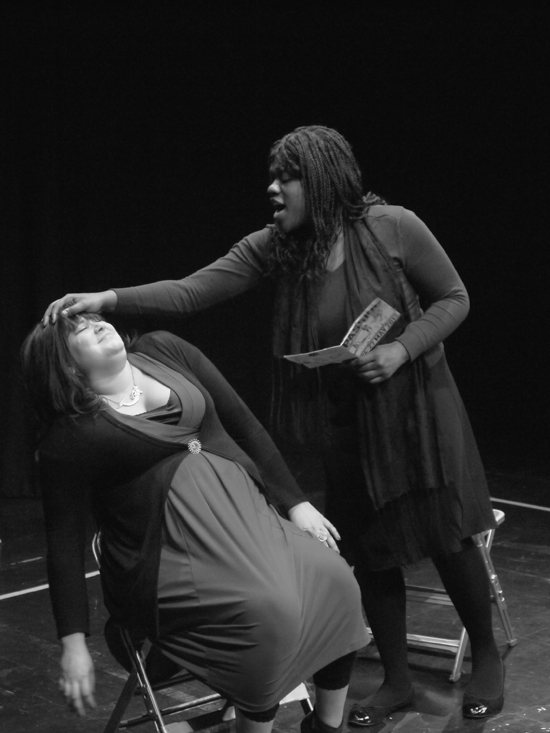 A black and white photo. The black female actor stands reading aloud from a book whilst holding her hand over the head of the seated white female actor, who squirms uncomfortably.