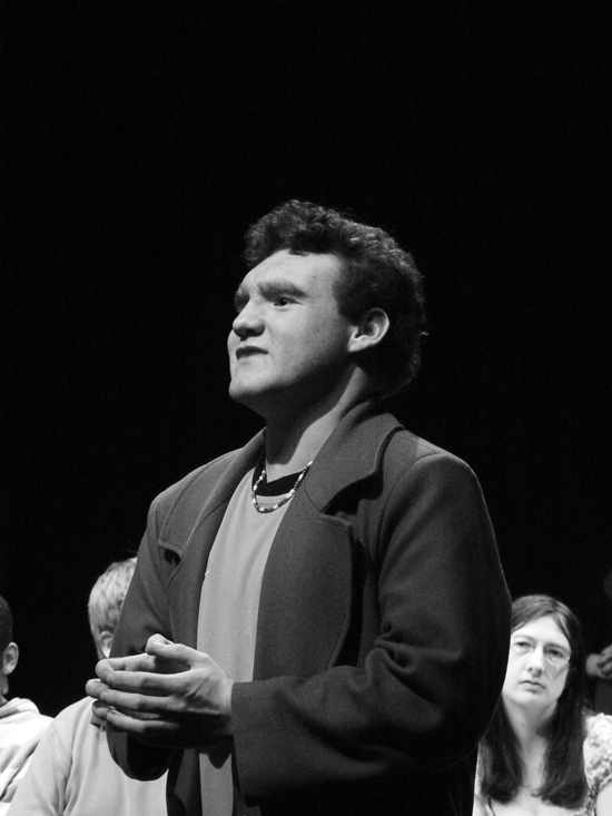 A close up of the young male white actor playing 'Teacher'. As he talks to the group, his hands are resting at his stomach with his fingers pressed lightly together. Photo in black and white.