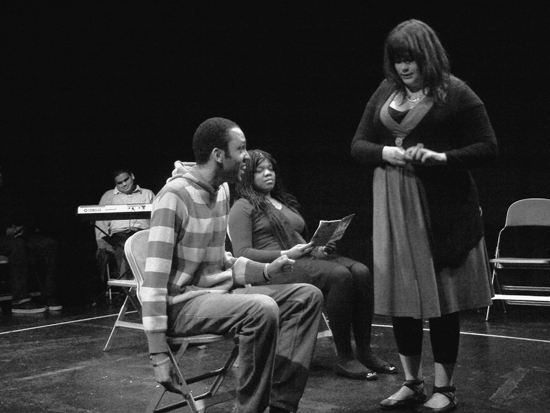 The young white female actor stands on the imaginary bus; a black male actor is seated talking to her as she plays with her fingers uncomfortably. The black female actor with the book looks on. Photo in black and white.