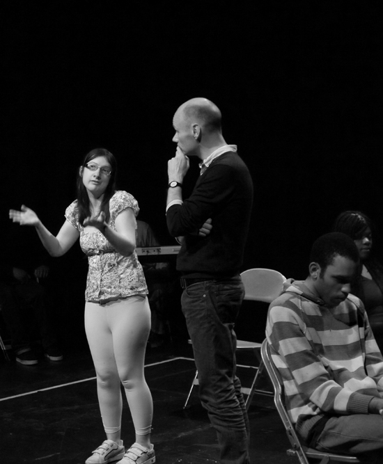 The director talks to a young white female actor who is expressing herself with hand gestures. Photo in black and white.