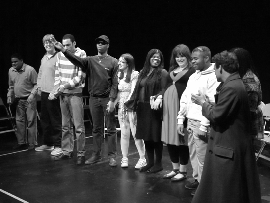 A shot of the whole group of actors in a line and smiling as if preparing for a final bow. Photo in black and white