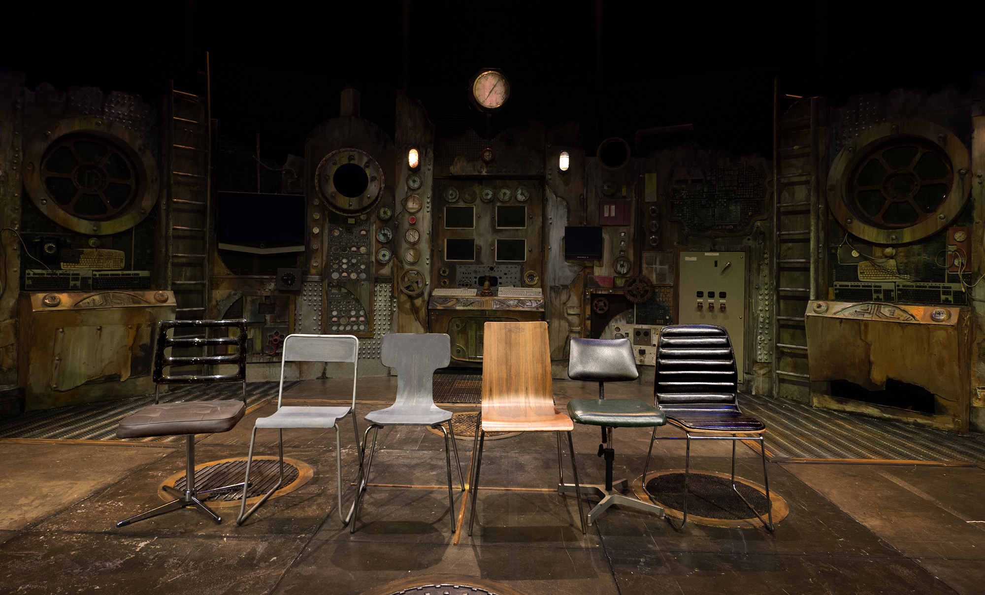 Six chairs lined up on stage in a variety of styles and shapes: some metal and wooden, another leathery and plush.