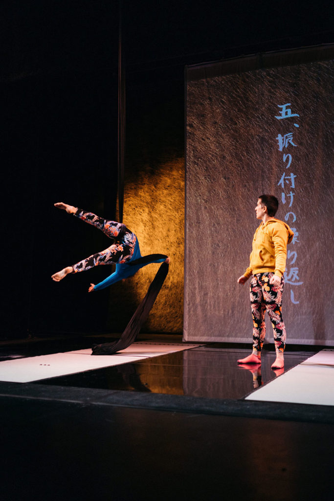 A wide portrait shot of a white woman in blue mid-fall from aerial silks while a white woman in yellow watches