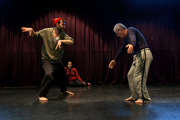 White male dance teacher and middle Eastern participant stand swinging their arms in a dance studio