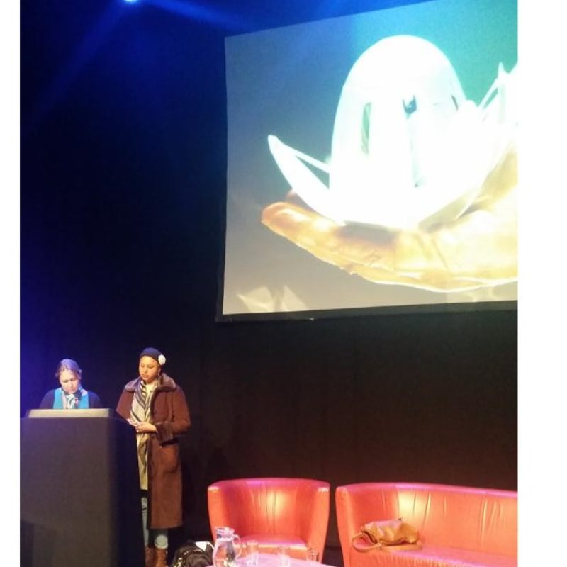 Maria Oshodi speaks on stage with a picture of the haptic lotus on screen above her