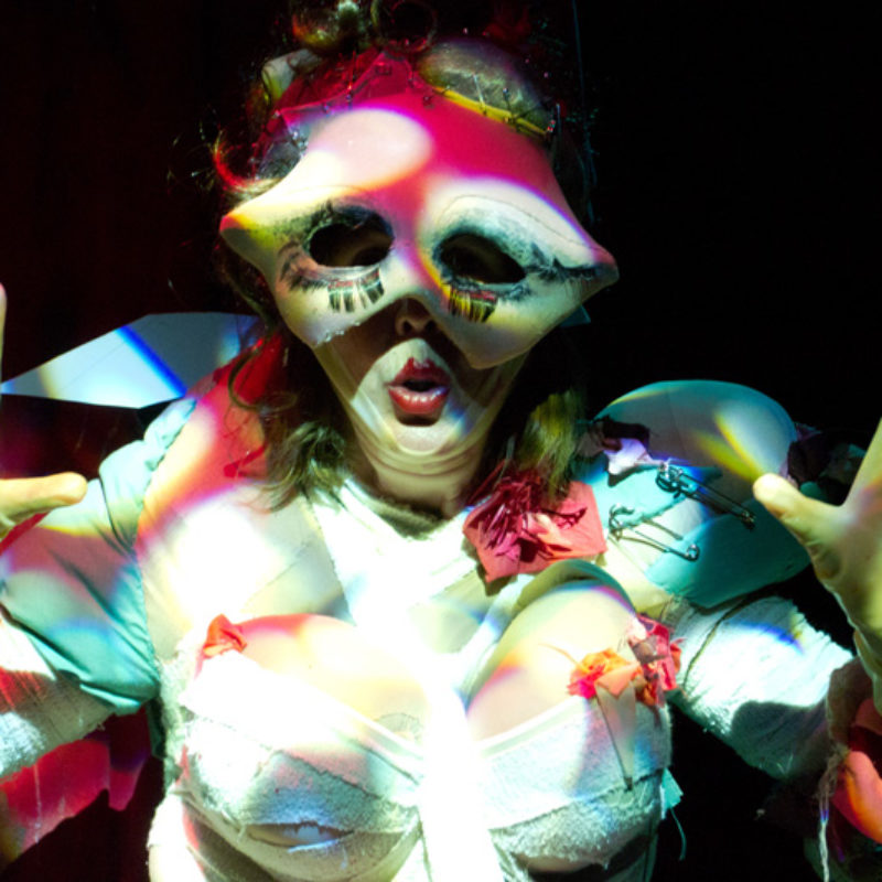 Burlesque image of Heather in a grotesque bodysuit with prosthetic boobs