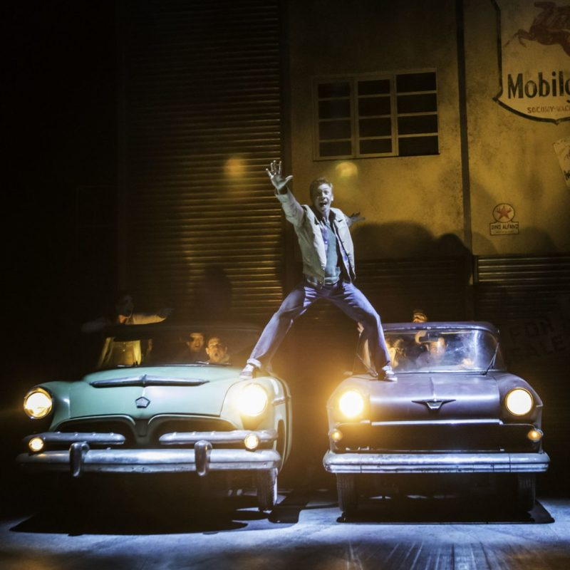 A man stands on top of two retro cars
