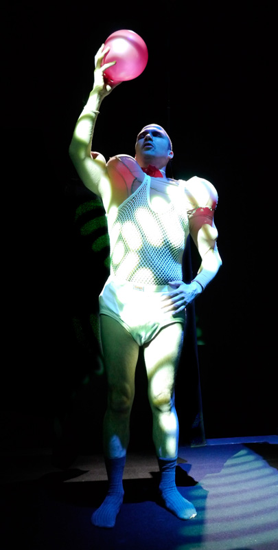 Tim performs as Cataracto in Sheer. Wearing a white fishnet outfit stuffed with inflatables to look like muscles, he stands like a Greek statue, holding up in one hand a bright pink balloon.