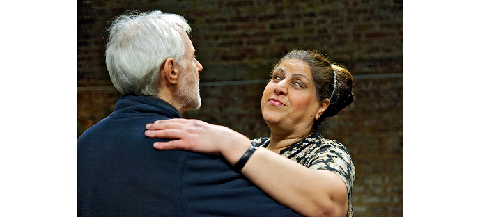 An older man and woman pictured from the shoulders up in ballroom hold