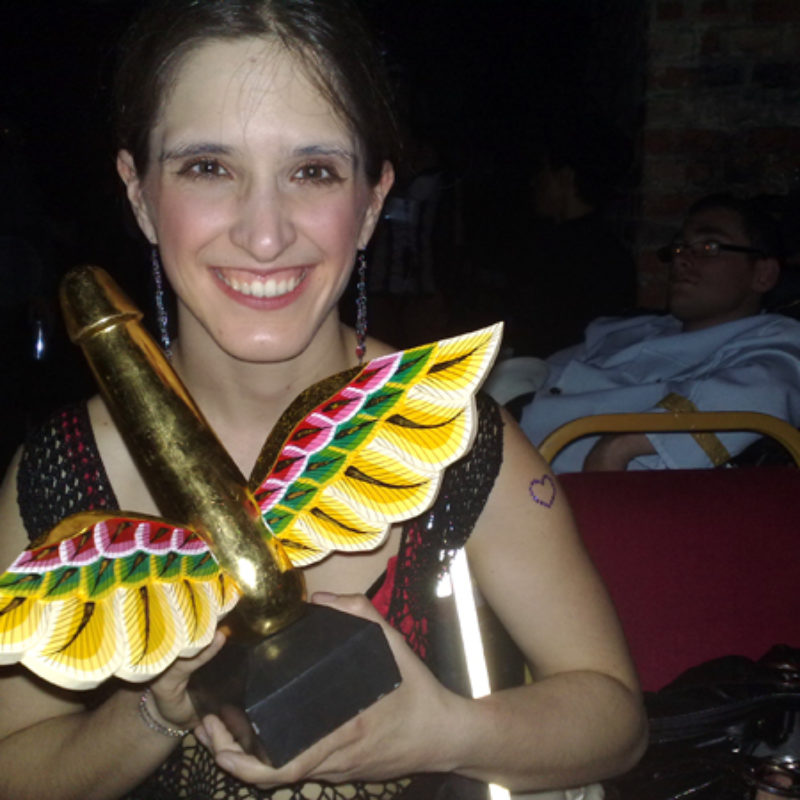 Amelia smiling - holds a gold winged phallus award