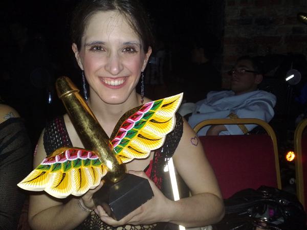 Amelia smiling - holds a gold winged phallus award