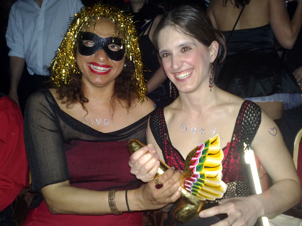 Maria in gold tinsel wig and black mask holding the winged award with Amelia broadly smiling