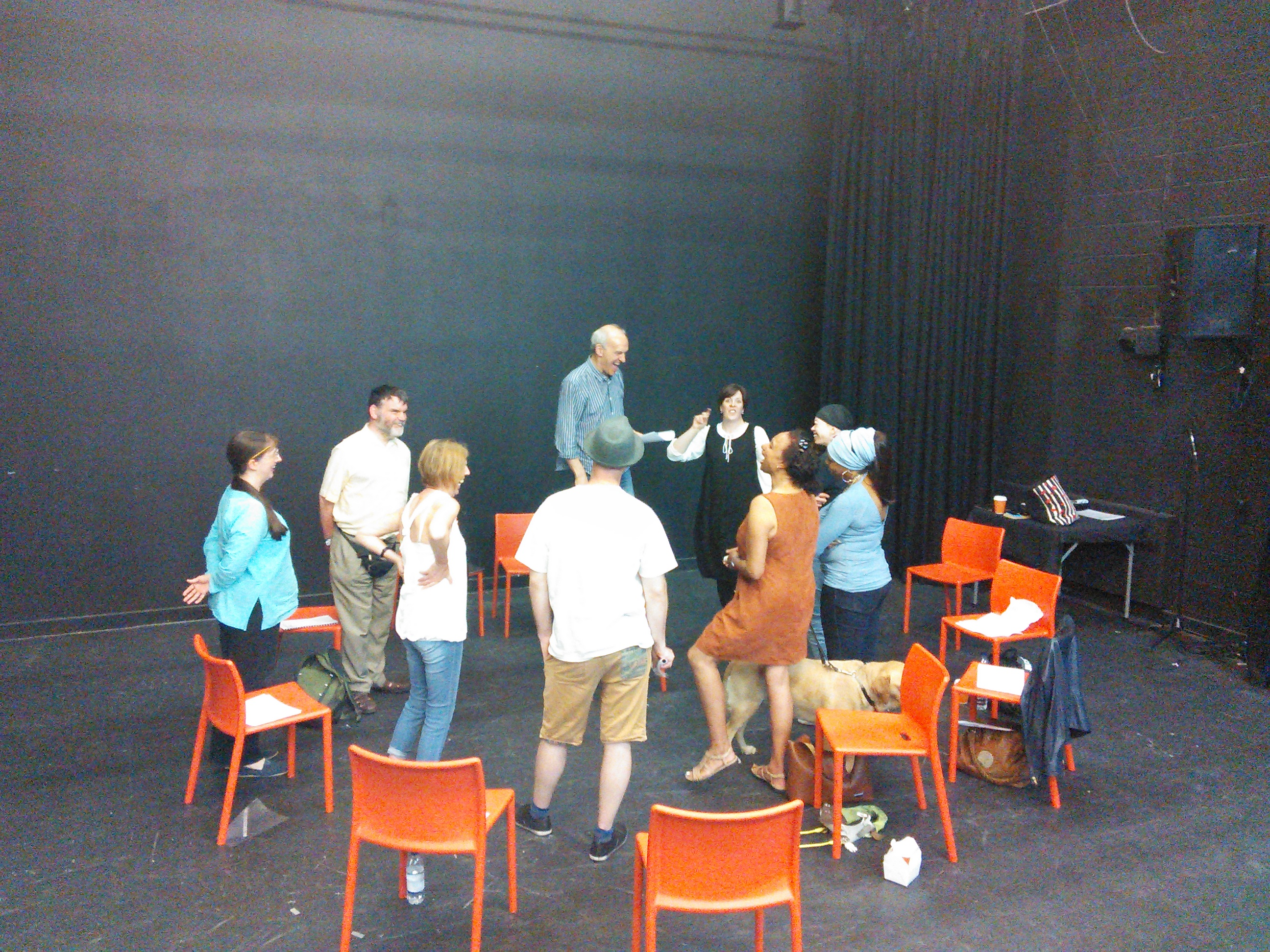 A group of nine people and a guide dog stand in a circle with high energy in a black box theatre