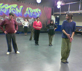 A group of adult participants in a line behind a dance teacher in a studio. Film about a participation project