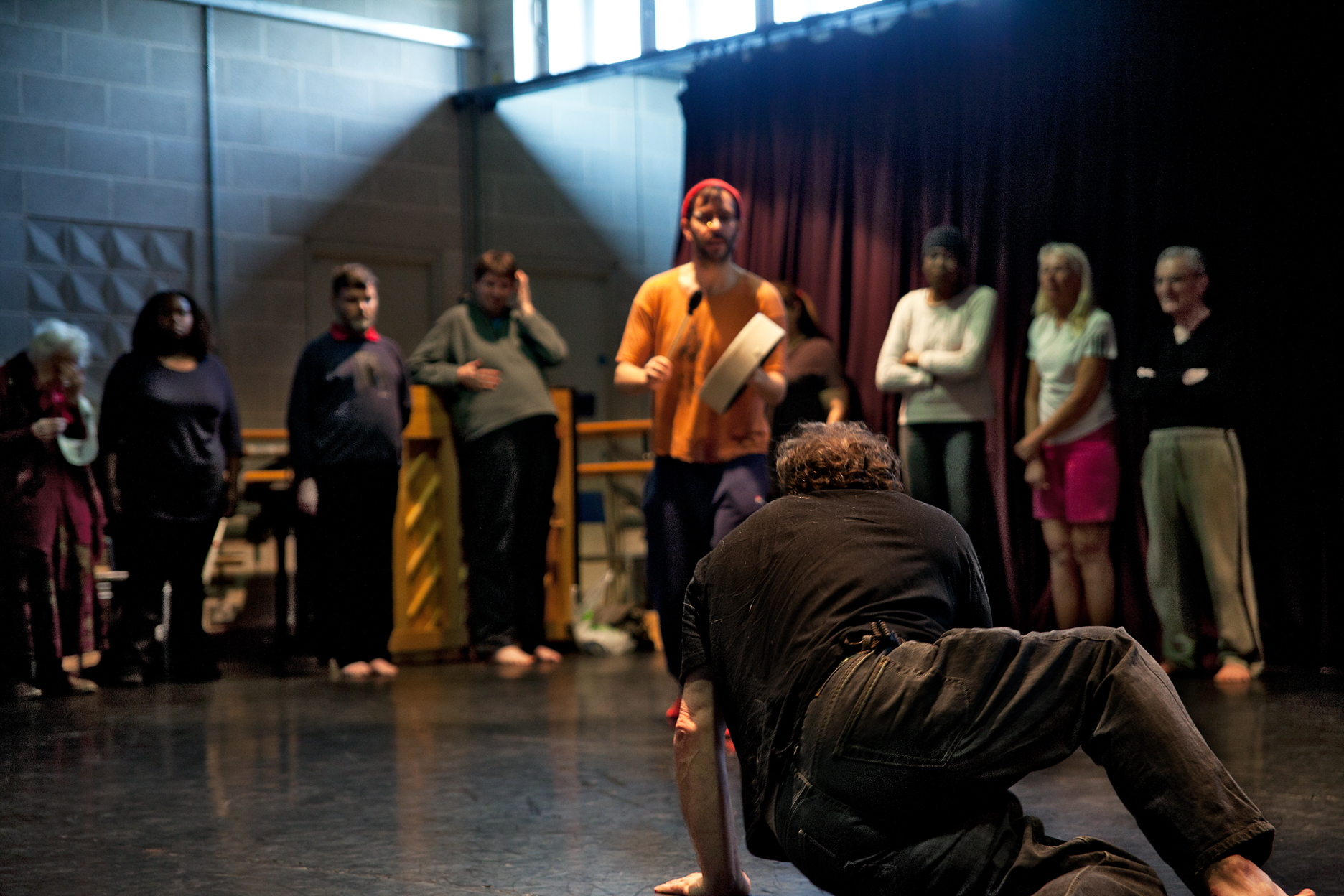 A group of people standing in a circle in a rehearsal room. Foreground, a man crouching on the ground with his back to the camera, facing the other participants.