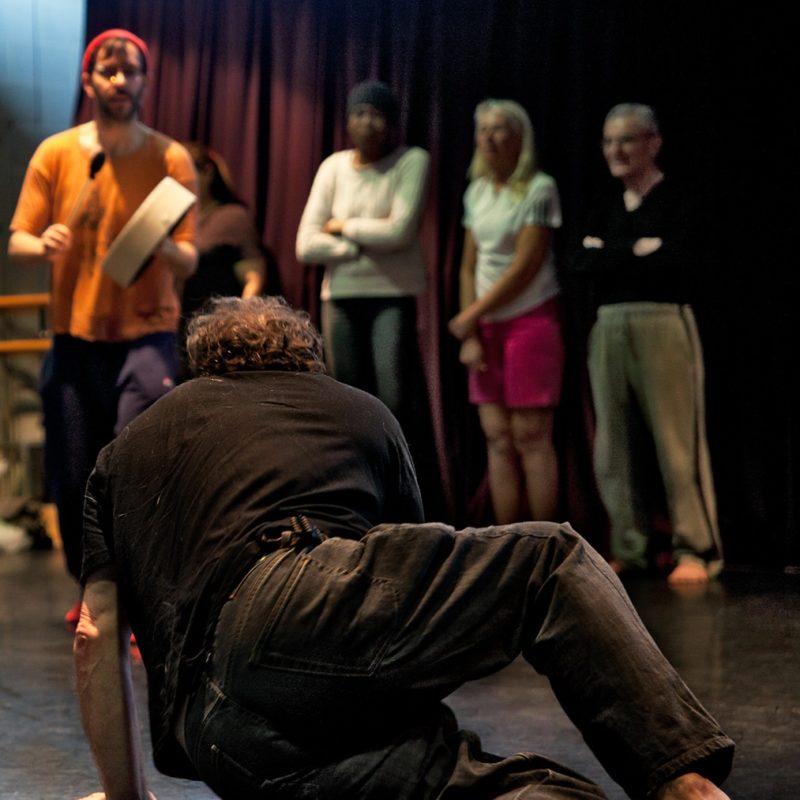 A man crawls athletically across the floor