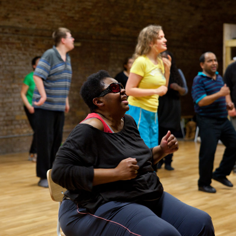 A black woman in sunglasses sits smiling as she joins in with a Zumba class from a chair