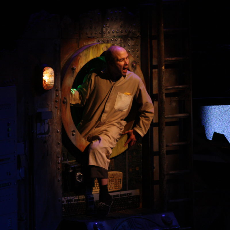 Tim as Old Man in Extant's 2016 tour of The Chairs. He sits in the porthole with the spotlight shining on him.