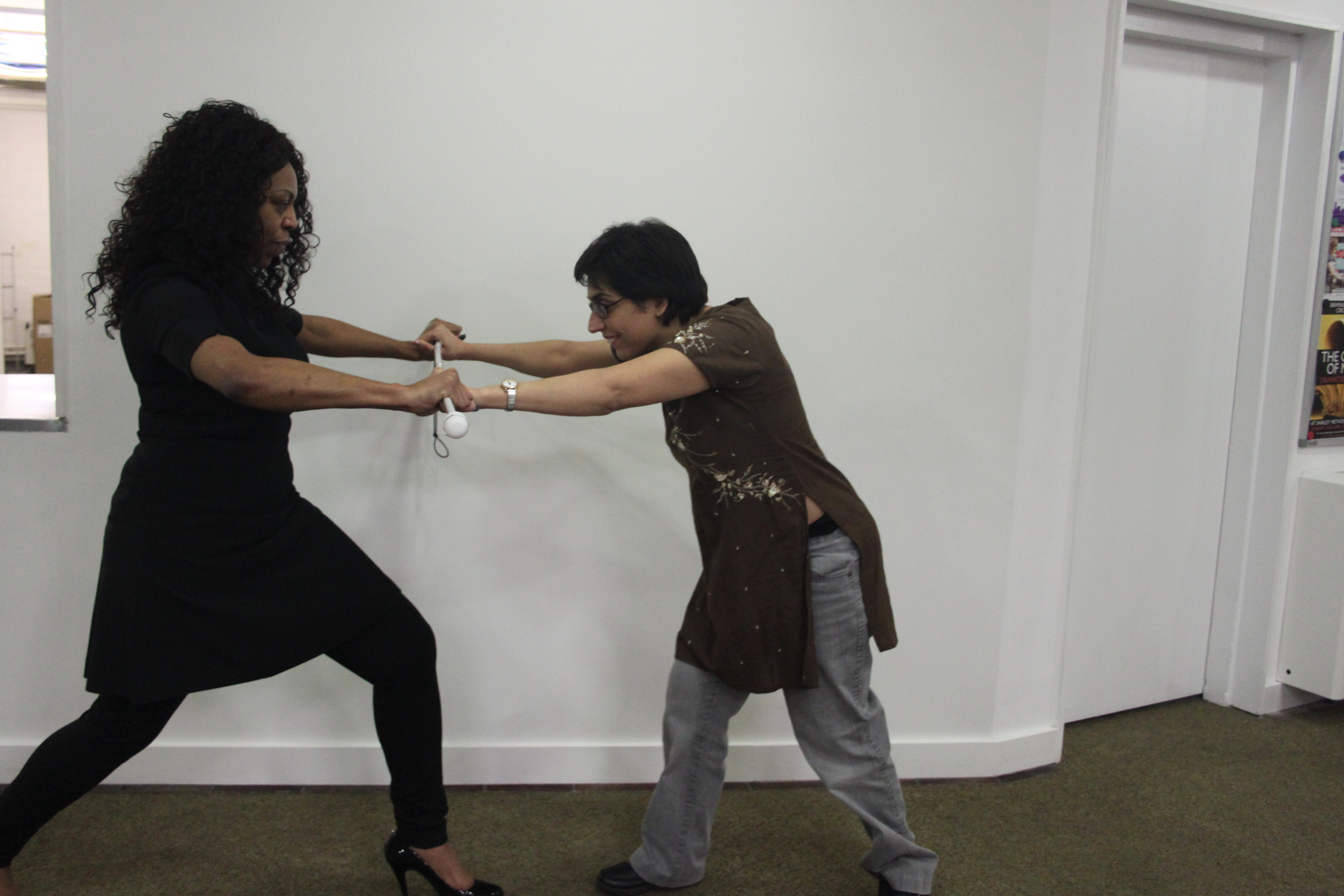two women facing opposite one another in lunge position, both holding on to a white cane acting as a bar in between them. One resists the push/pull of the other.