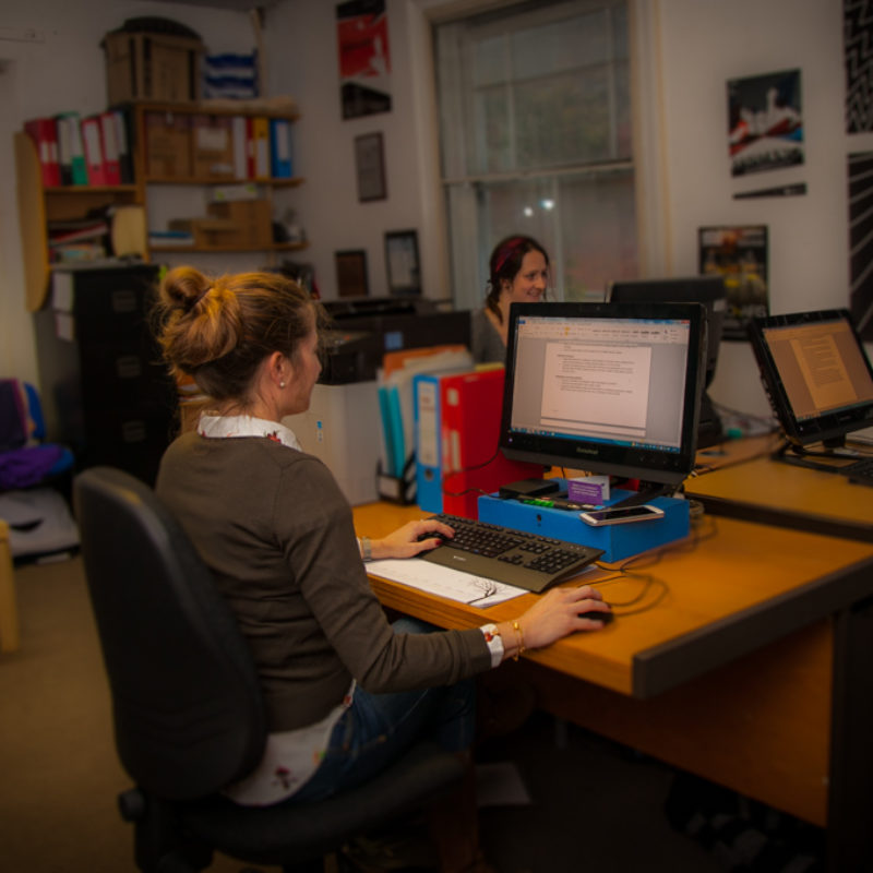 Three female team members sat working at desks in the Extant office