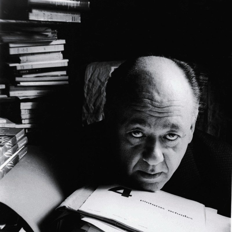 Absurd dramatist Eugene Ionesco rests his head on a pile of manuscript and journals