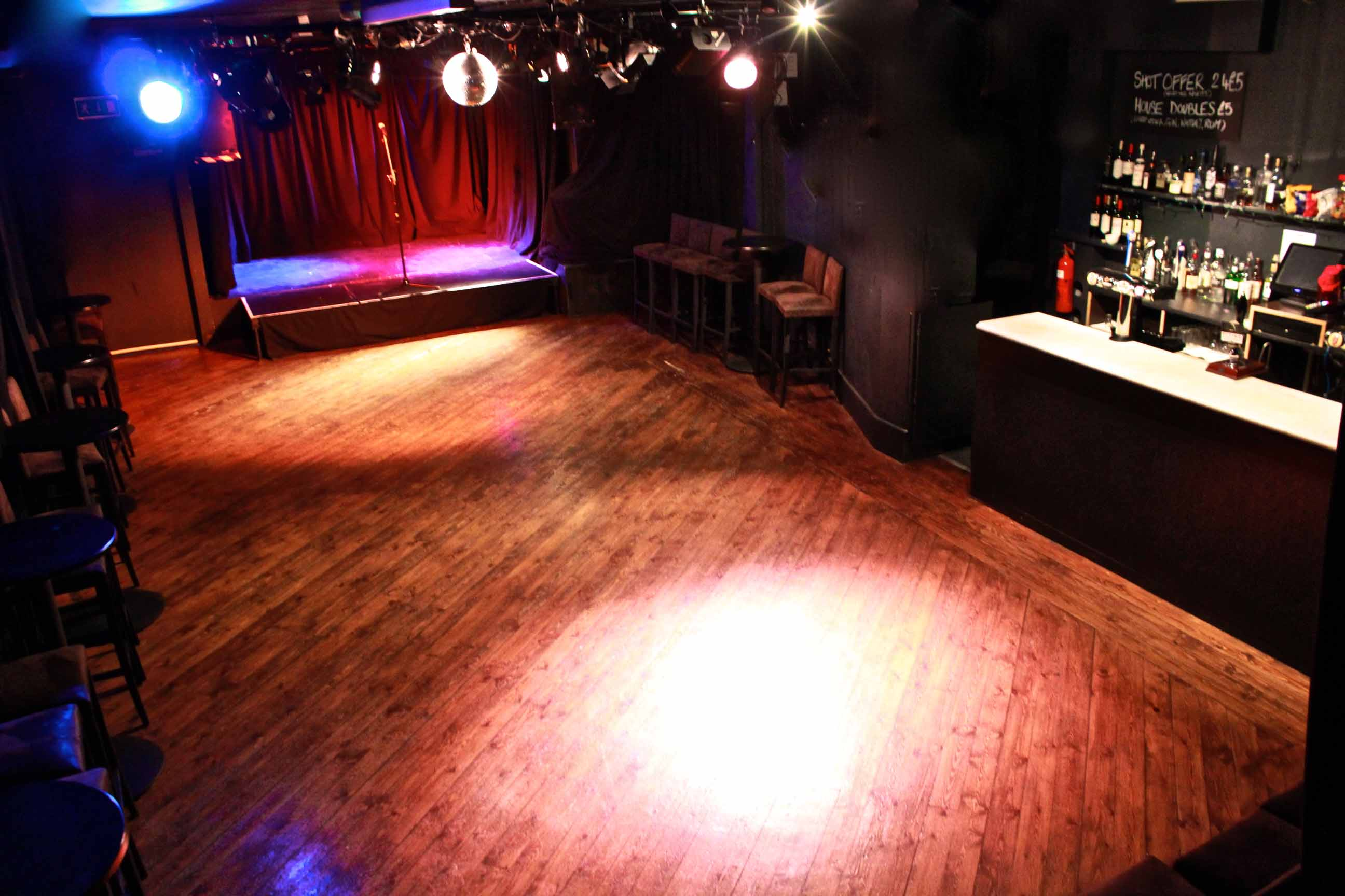 (from above) interior of the Komedia studio, without seating. stage lit up in red and purple