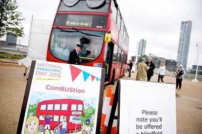 In the foreground a sign for ComBUStion with a cartoon of a red bus and children excited to board. Next to this sign is another saying 'Please note you'll be offered a blindfold.' In the background is the double decker Combustion bus with the conductor and members of the public standing beside it.