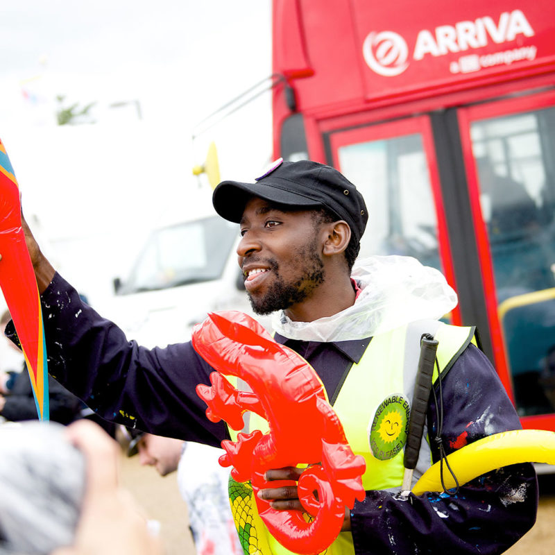 A man in dark blue mechanics uniform hands out brightly coloured inflatable animals