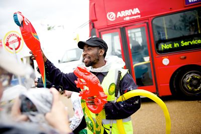A black male bus attendant holds out an inflatable parrot and lizard to attract passengers' attention. Behind him is the front of the bus and to his left a circular bus stop sign.
