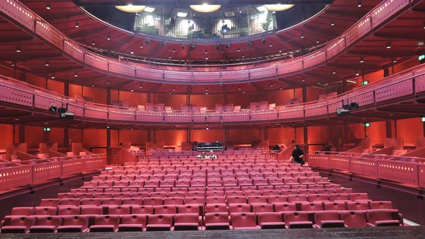wide shot from the stage of the Lowry auditorium (venue for the Chairs); three levels of empty red seats with Artistic director Maria Oshodi