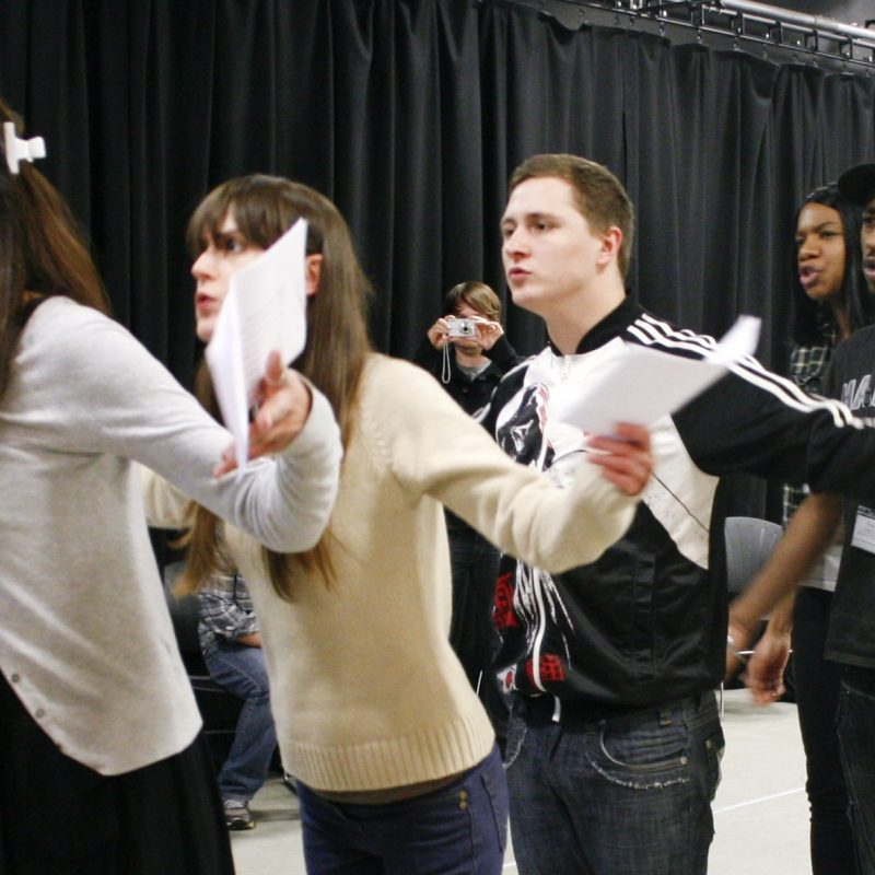 In rehearsal, five young people stand in a diagonal line, holding scripts. Their arms are gestured outwards and their mouths are open, as if talking to someone beyond the camera.