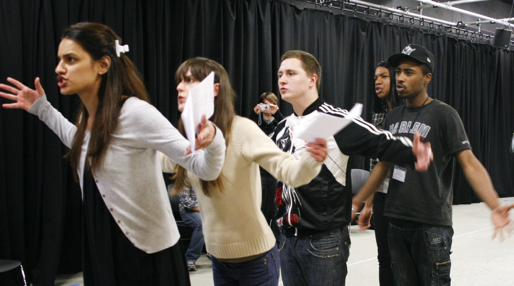 Five young people stand in a line rehearsing a phrase