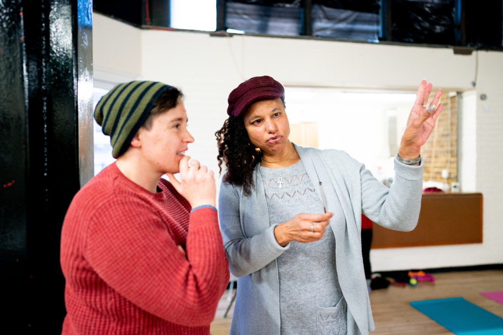 Two women stand in a rehearsal room and one in a copper coloured jumper and green striped beanie hat stands with her chin resting on her hands