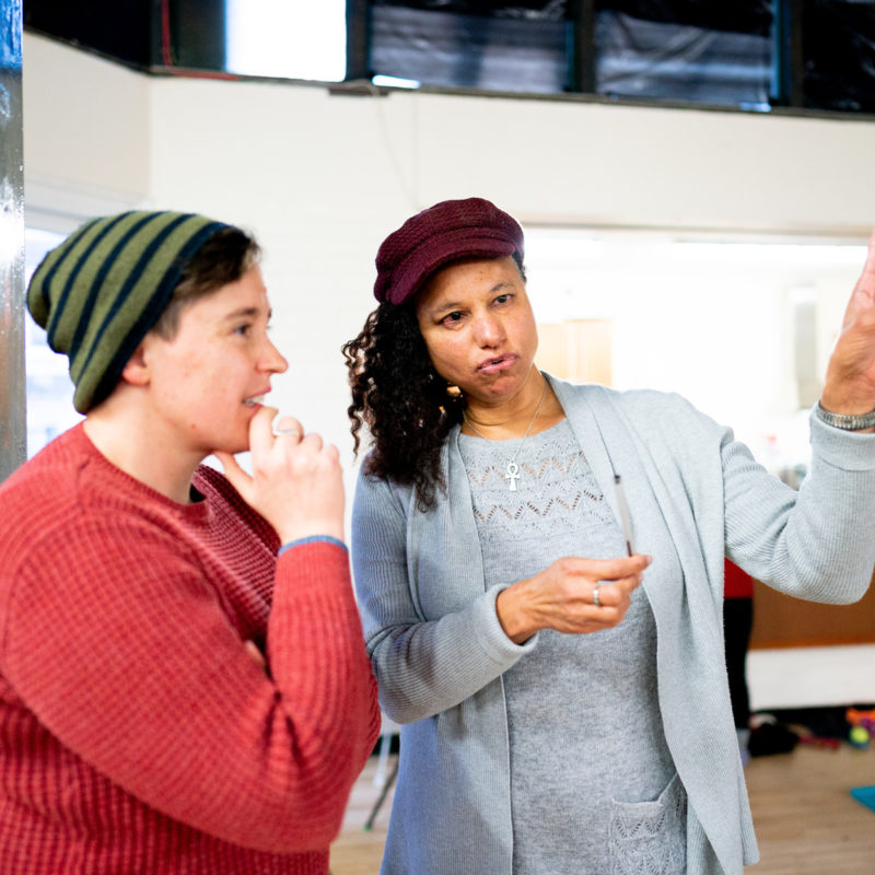 Two women stand in a rehearsal room - one in a copper coloured jumper and green striped beanie hat stands with her chin resting on her hands