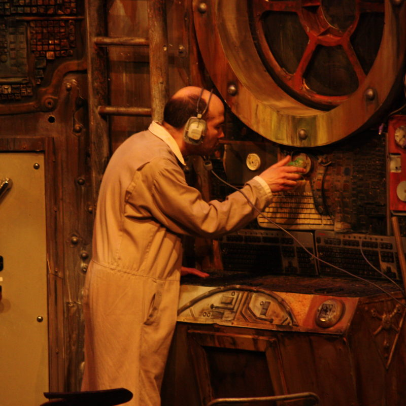 Scene from The Chairs 2016 - Old Man (Tim Gebbels) with headphones on turning a dial on a large control panel as if detecting radar signals