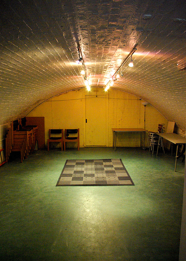 Interior of the Putney arches performance space, domed ceiling with simple lighting rig - laid out with carpet and chairs stacked either side