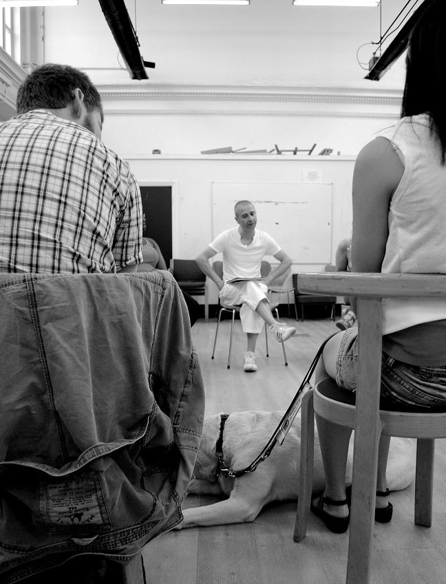 Two participants sit with their backs to us, a guide dog sits between them. They are facing the drama facilitator who can be seen between them, seated opposite talking thoughtfully. Black and white photo