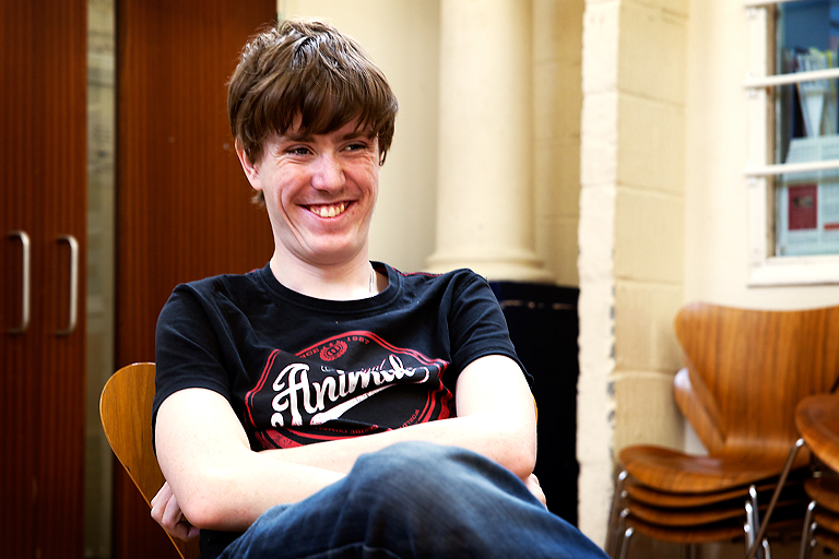 A young man with floppy hair is seated, with a broad smile, his arms crossed