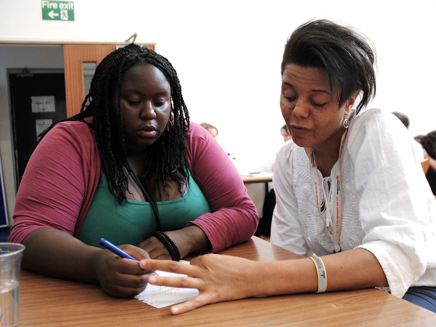 Two young women sit engrossed at a desk, the support worker is taking notes as the participant describes an idea