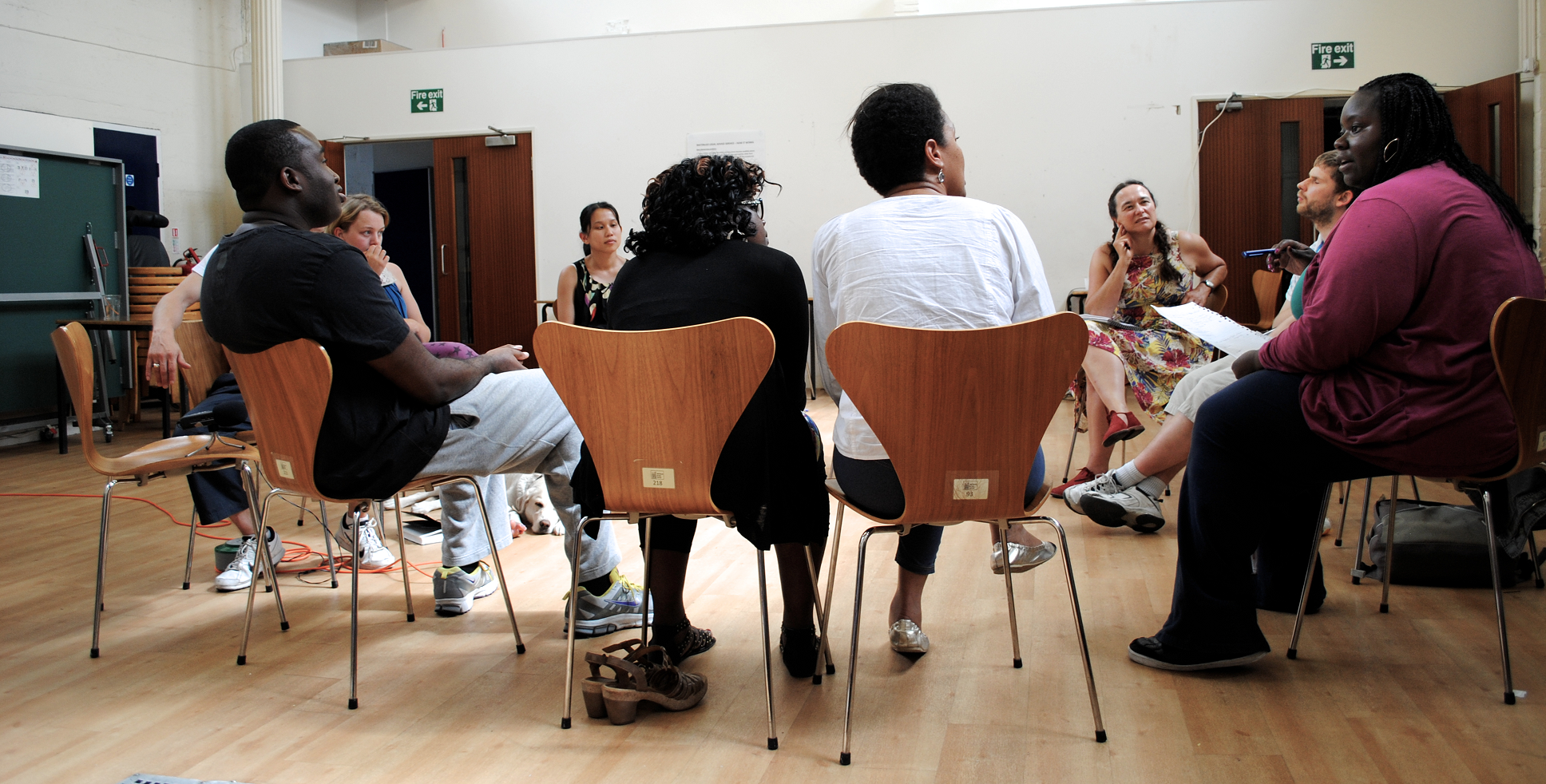 The view from outside a circle of chairs, the workshop group are listening to a woman talking on the right
