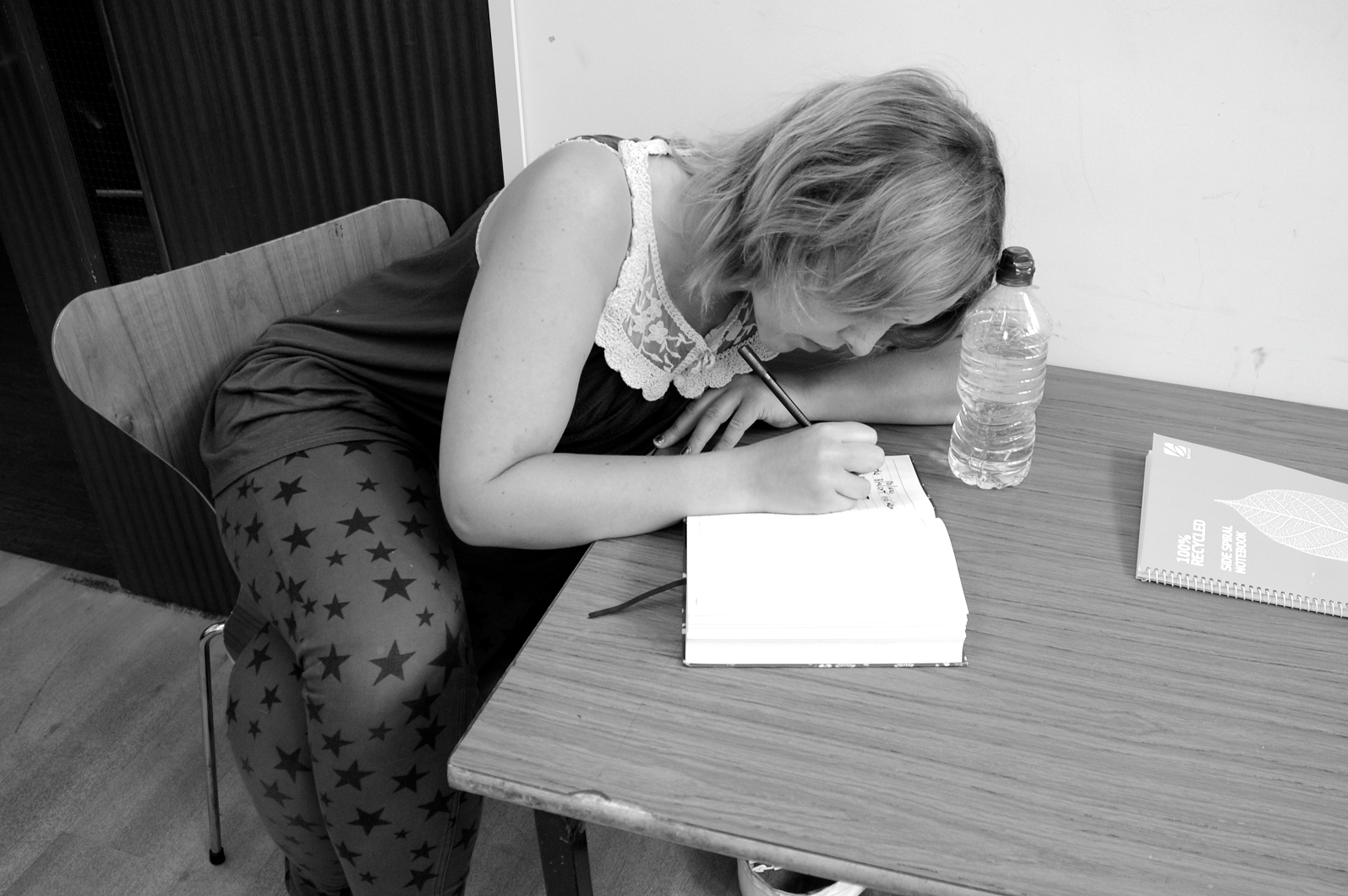 A white woman leans on a desk in concentration as she writes in a notebook. Black and white image